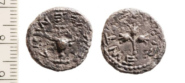 """Silver Half-Shekel coin. Obverse: A chalice from the Temple topped by the letter aleph, which means """"First year"""". Around it is inscribed """"Half a Shekel"""". Reverse: A stem with three pomegranates surrounded by the words """"Jerusalem the Holy"""".]"""